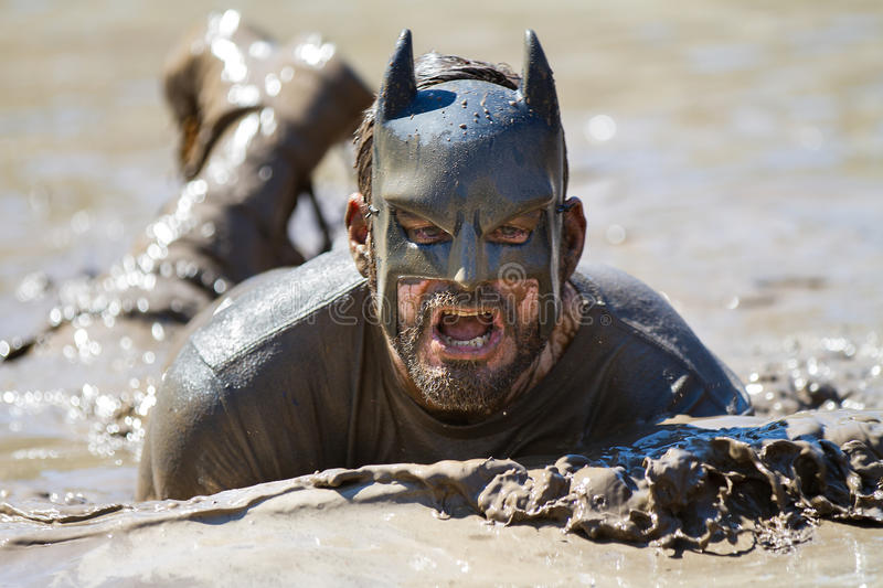 BOISE, IDAHO/USA - AUGUST 10: Runner dressed as batman swims in the mud during the The Dirty Dash in Boise, Idaho on August 10 royalty free stock photo