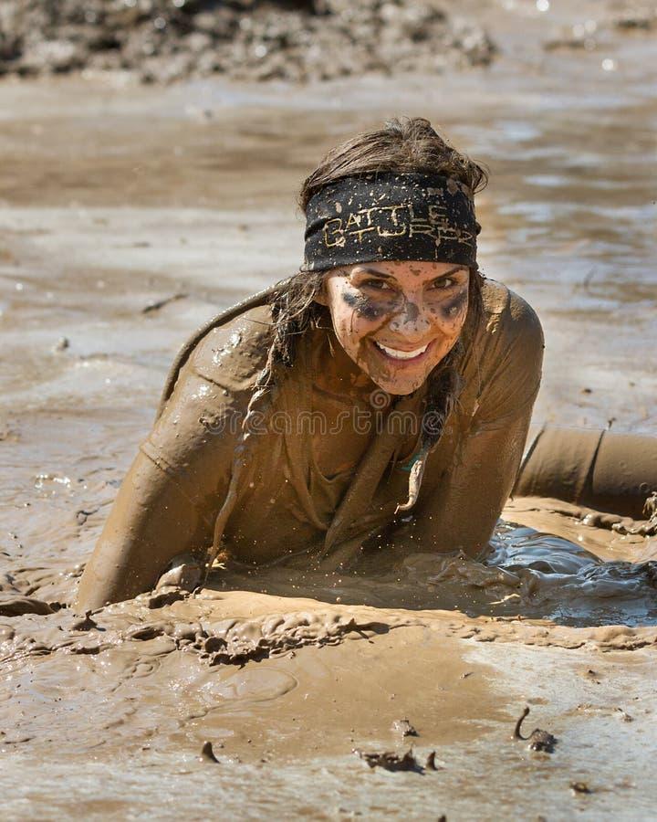 BOISE, IDAHO/USA - 25 de agosto - mujer no identificada se sienta en una charca del fango con una sonrisa enorme durante la rociad fotografía de archivo