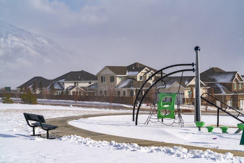 Boisko z wspinaczkowymi ramami przeciw domom i śnieżnej górze w zimie obrazy royalty free