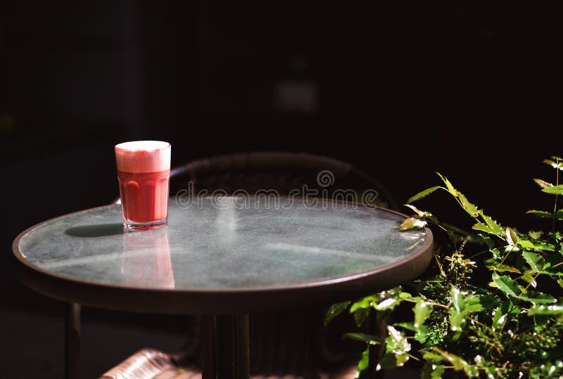 Boisson à la mode, latte rouge de café de baie avec la mousse sur la table transparente dans le café de rue photo libre de droits