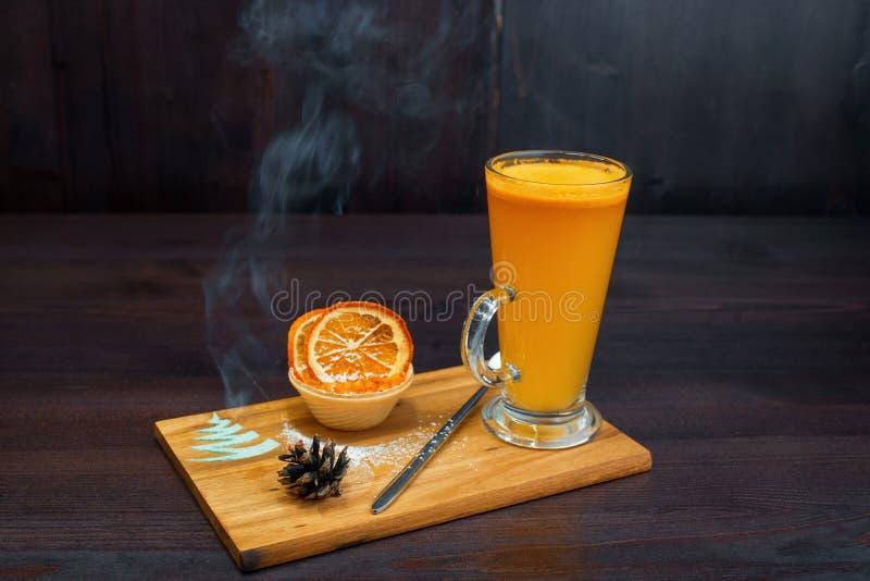 Boisson épicée chaude de thé de couleur jaune avec la confiture avec des tranches de positions oranges sèches sur la table sur un photo libre de droits