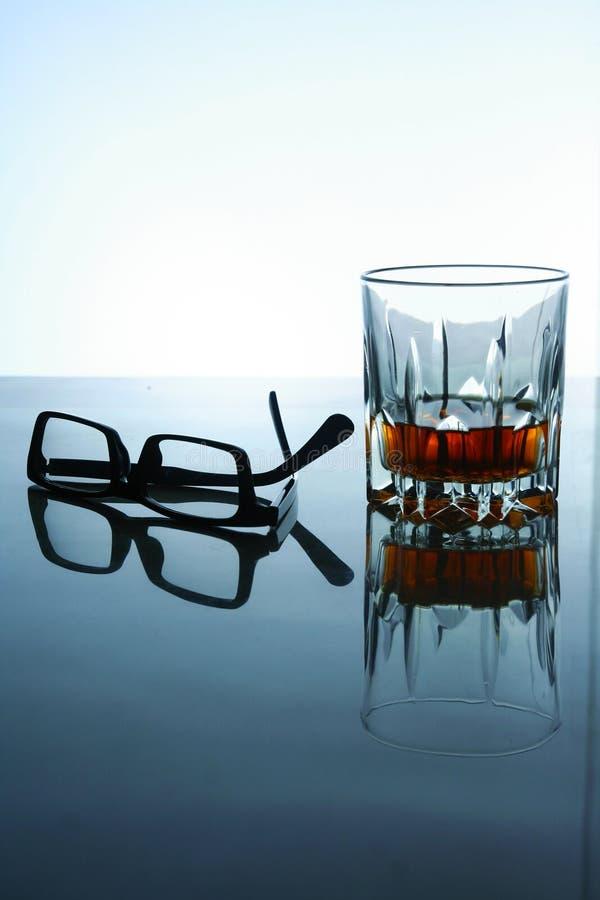 Boisson alcoolisée et une paire de lunettes images stock