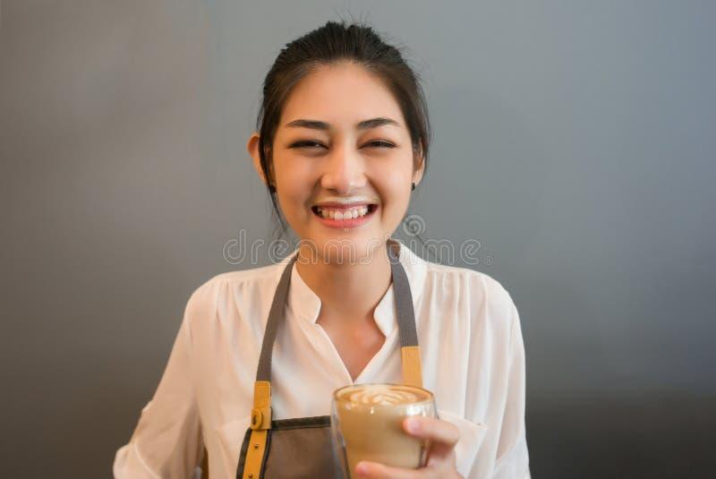 Boisson asiatique de sourire de femme de barman jeune à café un désordre MI photos libres de droits