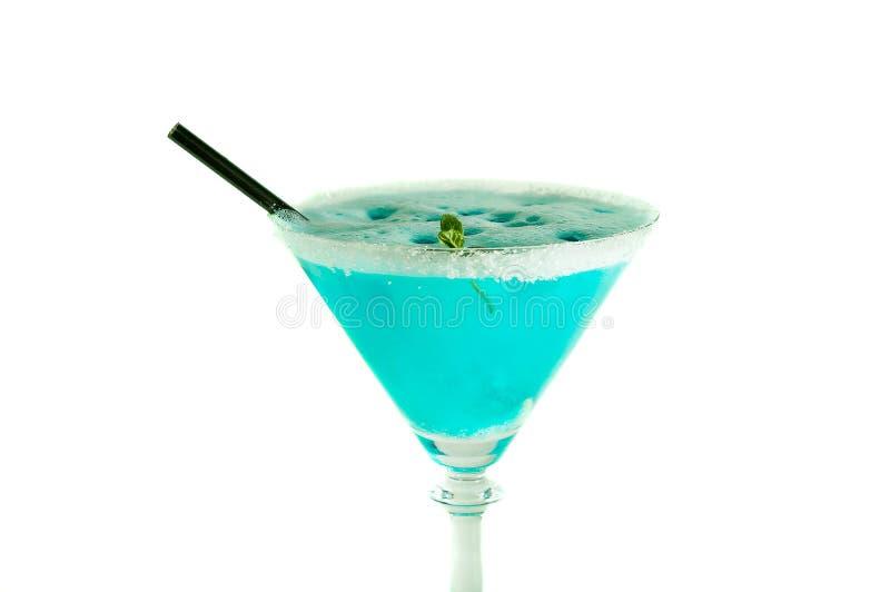 Boisson bleue d'alcool décorée du sucre et du bâton noir d'isolement sur le blanc photos libres de droits
