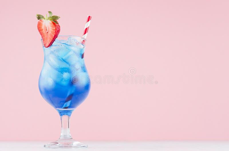 Boisson bleue d'alcool d'?t? avec la liqueur du Cura?ao, gla?ons, tranche de fraise, paille en verre de charme sur le fond rose-c photographie stock libre de droits