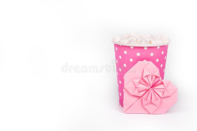 Boisson chaude avec la guimauve dans la tasse de papier rose Carte rose de tasse de papier et de valentine sur le fond blanc Conc photographie stock libre de droits