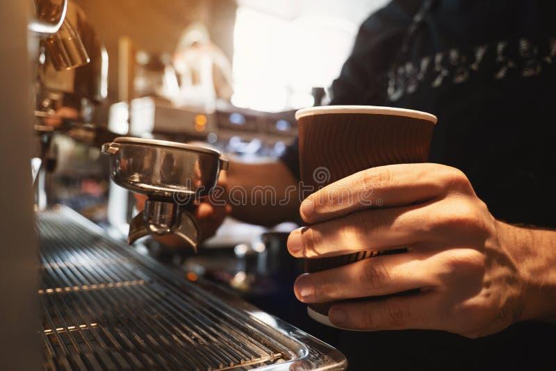 Boisson chaude de café de participation d'homme de barman dans la tasse de papier dans un support de main et de café dans une aut image libre de droits