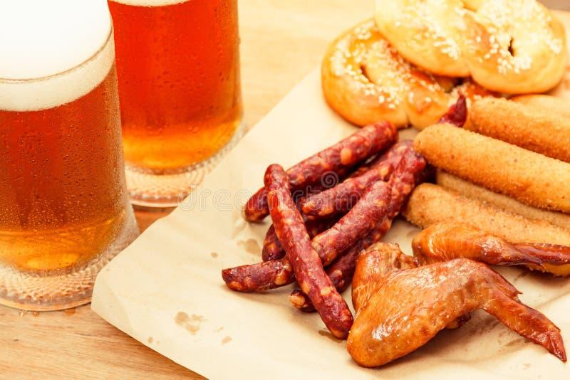 Boisson d'alcool en verre de bière avec la saucisse de nourriture, fond de bar photos libres de droits