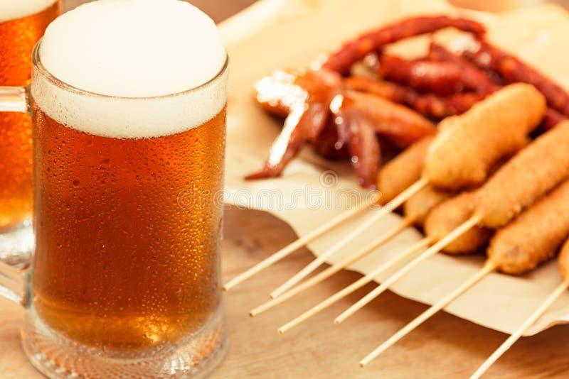 Boisson d'alcool en verre de bière avec la saucisse de nourriture, panneau de bar image libre de droits