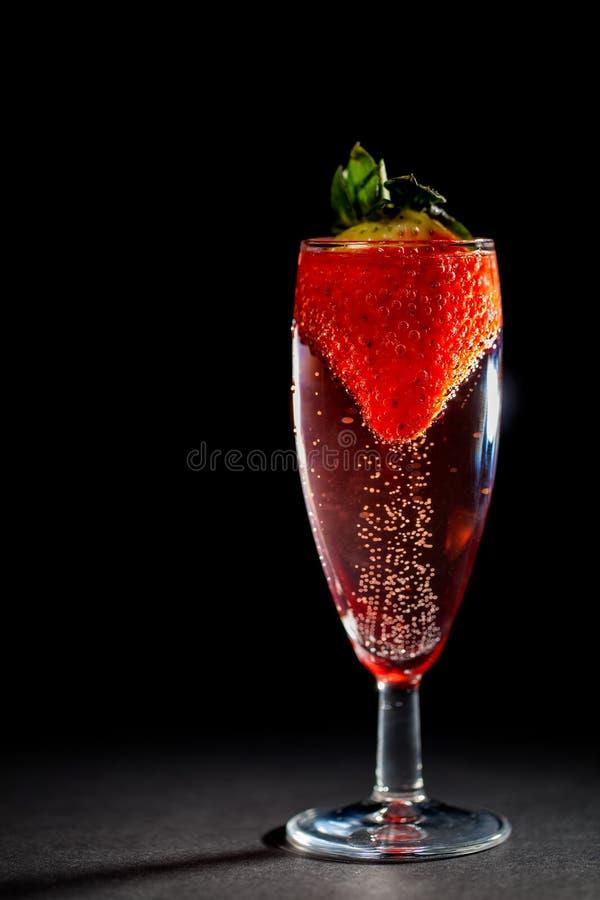 Boisson de célébration Verre rose pétillant de champagne avec la fraise photographie stock libre de droits