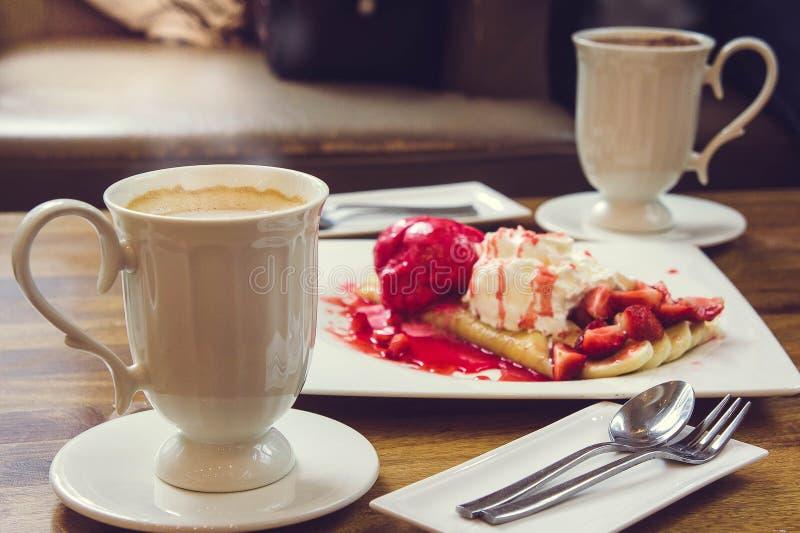 Boisson de café et crêpe chaudes de fraise de crème glacée sur la table en bois dedans photos stock