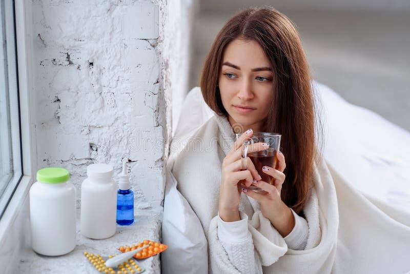 Boisson de chauffage potable de femme malsaine malade à l'intérieur Froid et grippe Plan rapproché de belle jeune fille avec la t photos stock