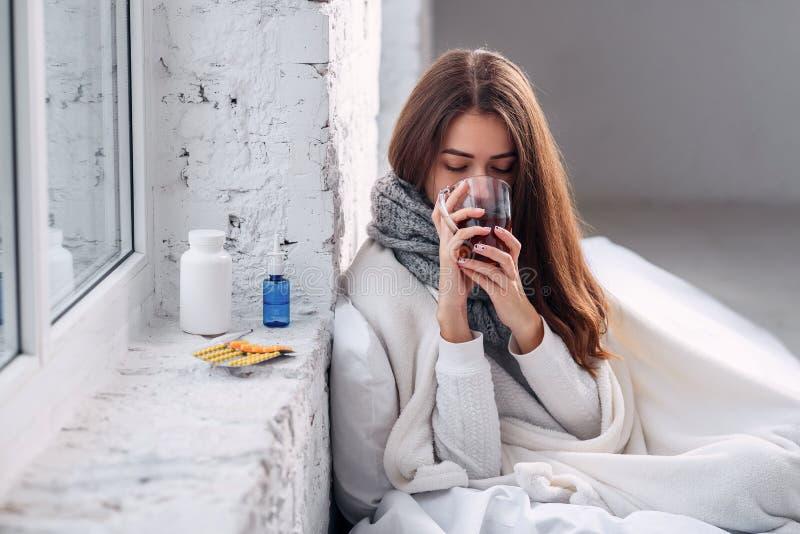 Boisson de chauffage potable de femme malsaine malade à l'intérieur Froid et grippe Plan rapproché de belle jeune fille avec la t images libres de droits