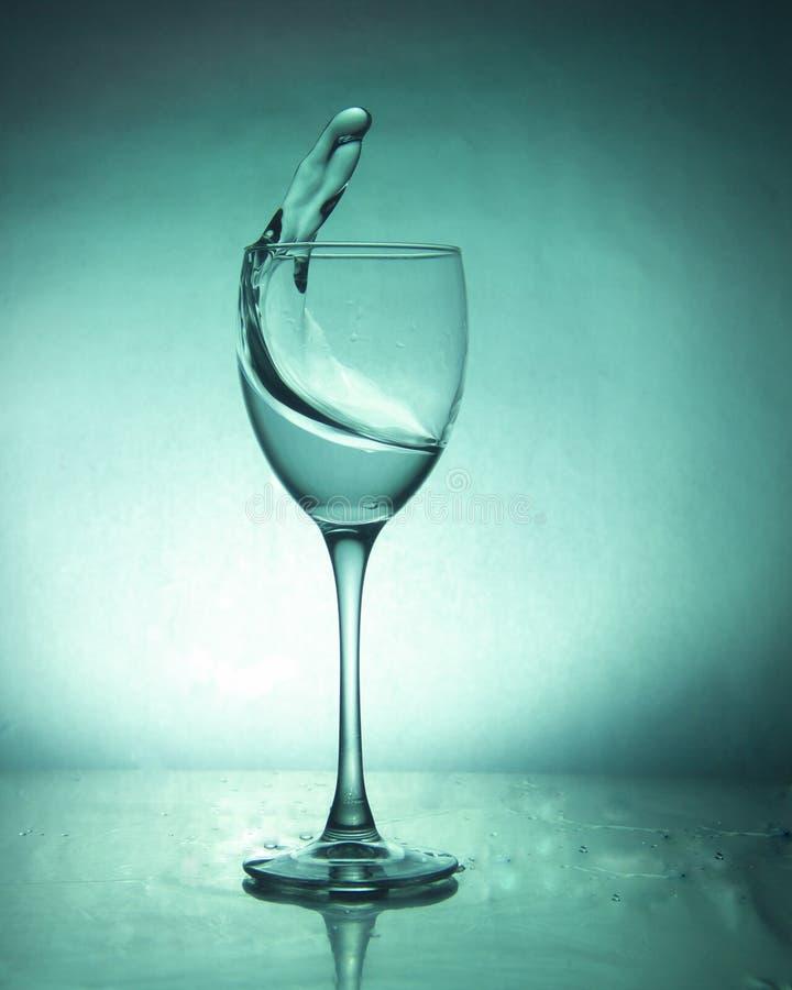 Boisson de luxe d'éclaboussure dans un verre sur une jambe élevée sur un fond coloré photos stock