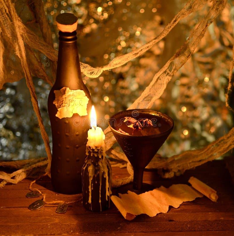 Boisson de sorcière avec la bougie brûlante dans l'obscurité image libre de droits