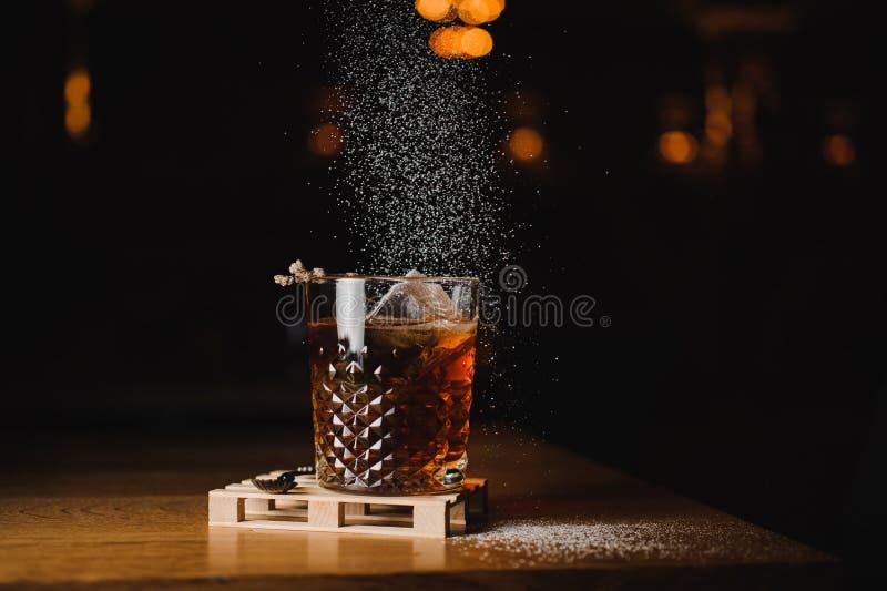 Boisson de whiskey de saupoudrage avec de la glace sur le bois dans la barre photographie stock libre de droits