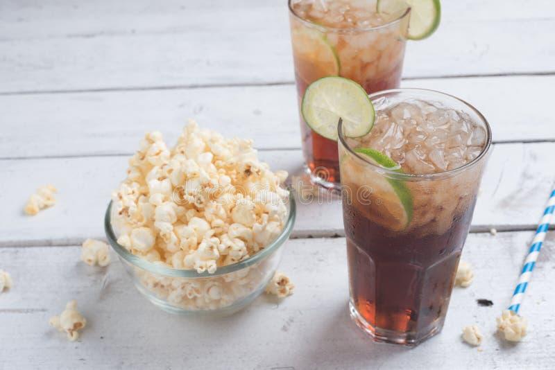 Boisson et maïs éclaté de kola dans le bol en verre sur la table blanche image libre de droits