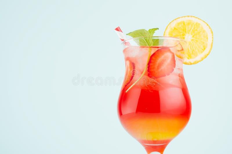 Boisson exotique posée froide avec l'orange, glace, fraise, menthe dans le verre à vin à l'arrière-plan vert en pastel, plan rapp images stock