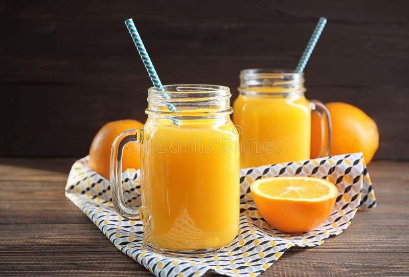 Boisson fraîche d'agrume dans des pots et l'orange de maçon sur la table photo stock