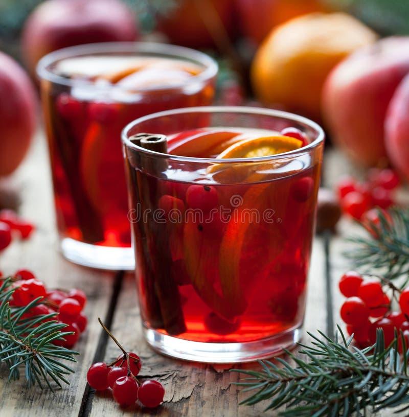 Boisson la soirée d'hiver Poinçon de grenade ou vin chaud orange granberry chaud, sangria dans une table en bois rustique images stock