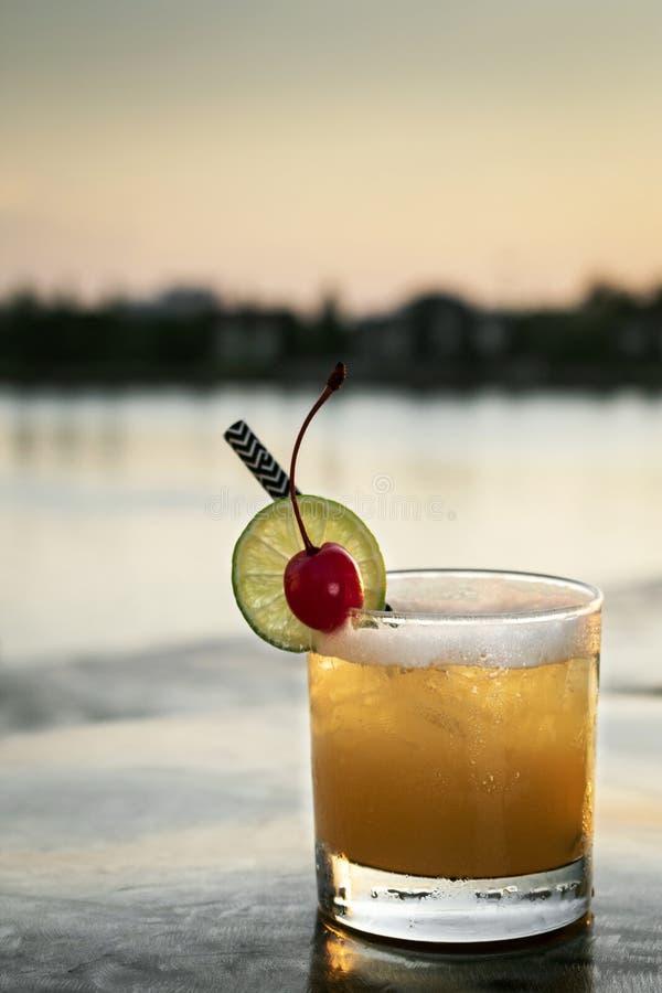 Boisson mélangée de cocktail de vodka de tournevis de pêche dehors au coucher du soleil photo stock