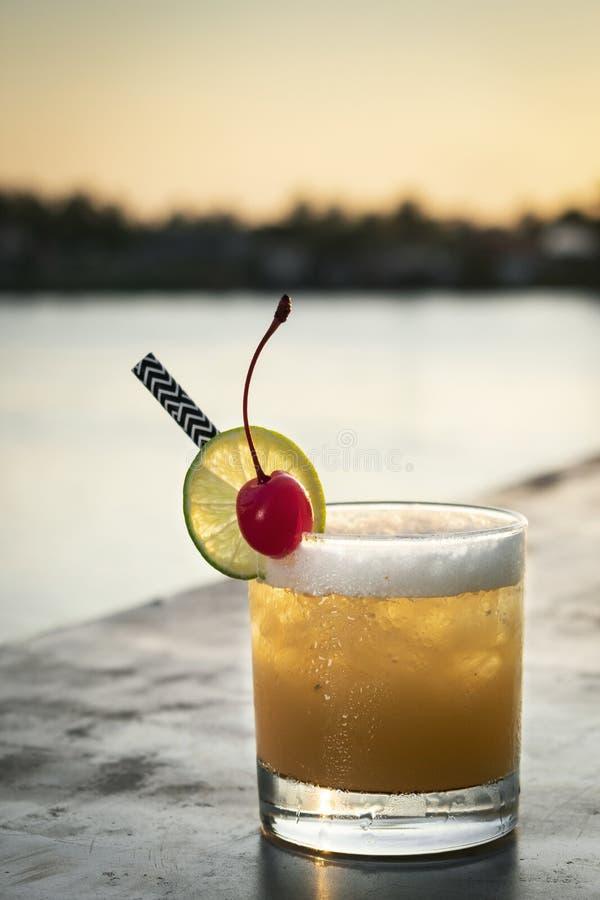 Boisson mélangée de cocktail de vodka de tournevis de pêche dehors au coucher du soleil images stock