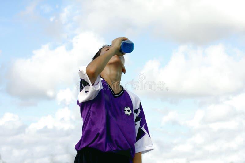 Boisson régénératrice potable de garçon altéré photo libre de droits