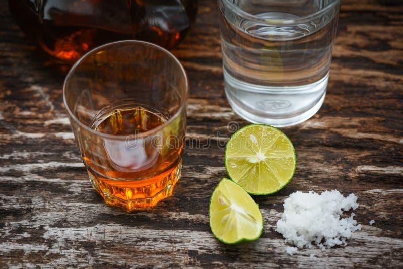 Boissons alcoolisées et sel de citron sur le fond en bois rustique - eau-de-vie fine dans un verre avec de l'eau les bouteilles e image libre de droits
