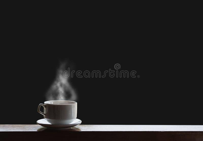 Boissons chaudes avec la vapeur sur la table en bois, d'isolement sur le fond noir images libres de droits