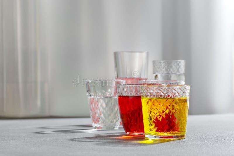 Boissons colorées dans des tasses en verre sur un fond gris images stock
