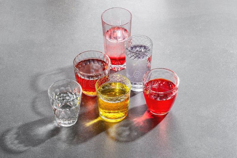 Boissons colorées dans des tasses en verre sur une table en pierre grise photographie stock libre de droits