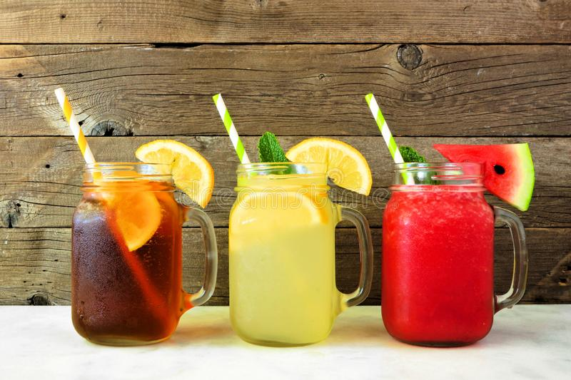 Boissons d'été de jus de thé glacé, de limonade et de pastèque en verres de pot de maçon contre le bois foncé photographie stock libre de droits