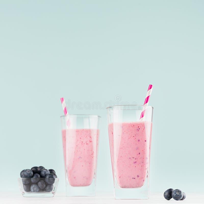 Boissons de lait de régime en verre élégant avec les myrtilles dans la cuvette, pailles rayées sur le fond bleu-clair mou en  image stock
