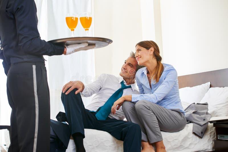 Boissons de portion de page d'hôtel aux couples d'affaires photographie stock