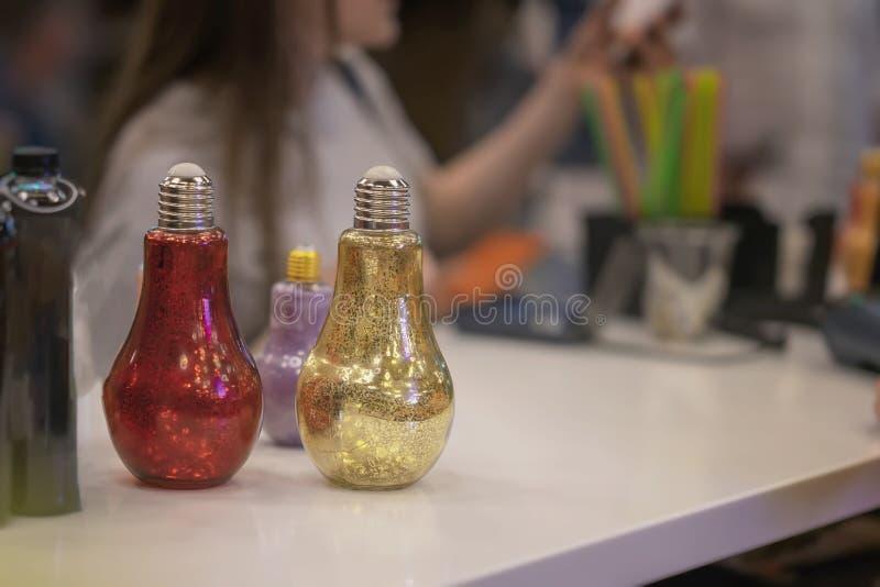 Boissons en verrerie populaire brillante sous forme d'ampoule électrique sur le compteur de barre, dans de fond brouillé photographie stock