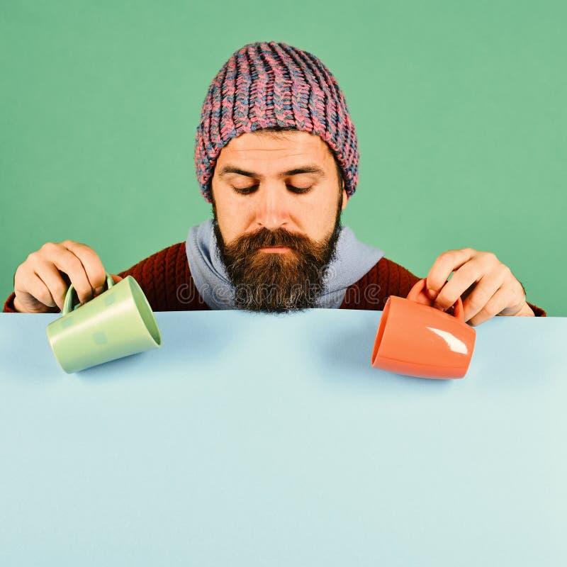 Boissons et temps confortable de saison L'homme dans le chapeau chaud tient les tasses oranges et vertes images libres de droits