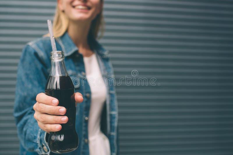 Boissons, les gens et concept de mode de vie - fin de la femme heureuse buvant avec la paille près du mur gris image stock