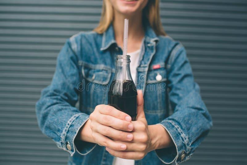 Boissons, les gens et concept de mode de vie - fin de la femme heureuse buvant avec la paille près du mur gris photos stock