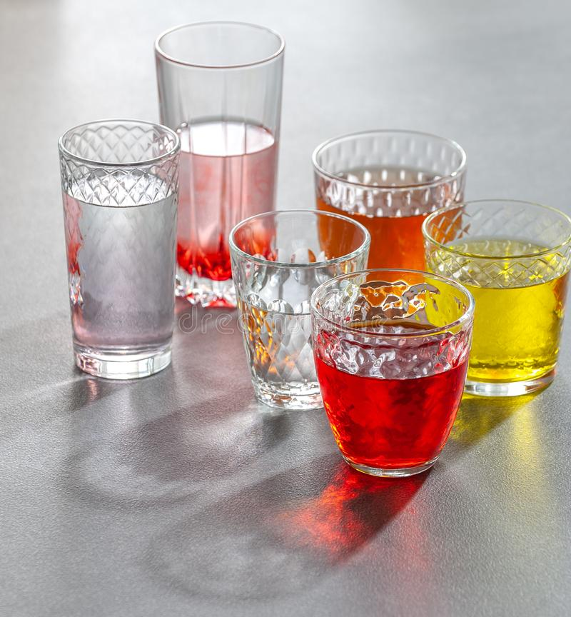 Boissons non alcoolisées colorées en verres facettés en verre sur une table grise Photo avec un fond de gradient image stock