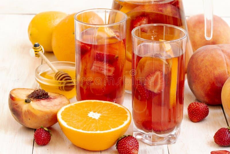 Boissons r?g?n?ratrices d'?t? Fruit, cocktail de baie compote avec la pêche, fraise, orange, hioney Fruit et baie froids images stock