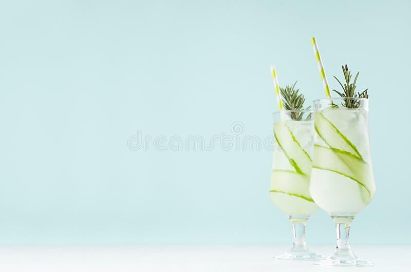 Boissons saines fraîches froides tropicales de chaux et de concombre avec des glaçons, paille, romarin sur le fond vert clair mou photographie stock libre de droits