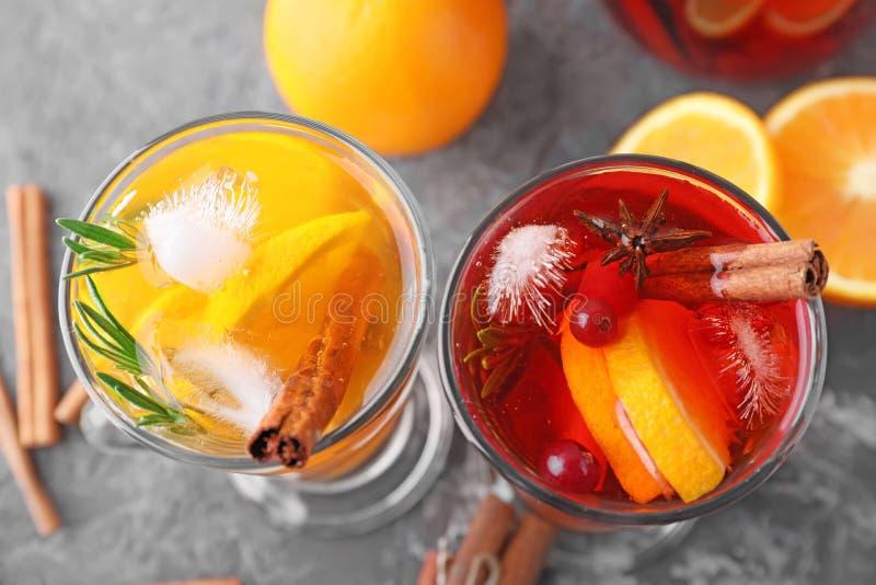 Boissons savoureuses avec l'orange et la cannelle dans des tasses en verre sur la table photos libres de droits