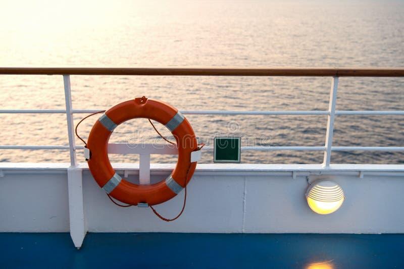 Boj eller livbojcirkel på shipboard i aftonhavet i miami, USA Flytandeapparat på skeppsida på seascape Säkerhet räddningsaktion,  royaltyfri fotografi