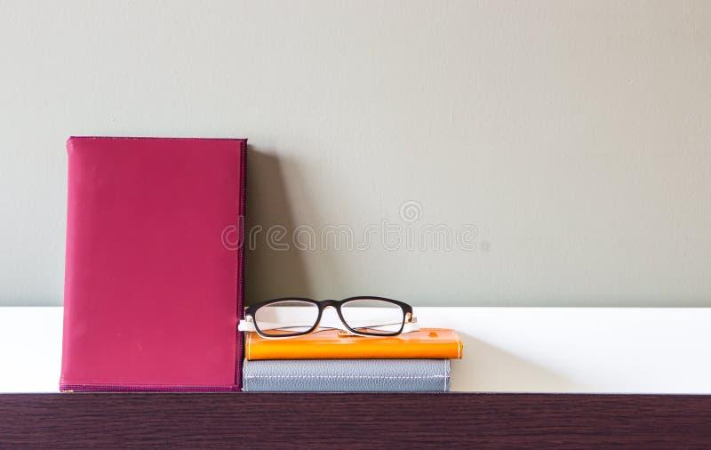 Bok, anteckningsböcker och exponeringsglas på hylla arkivbild