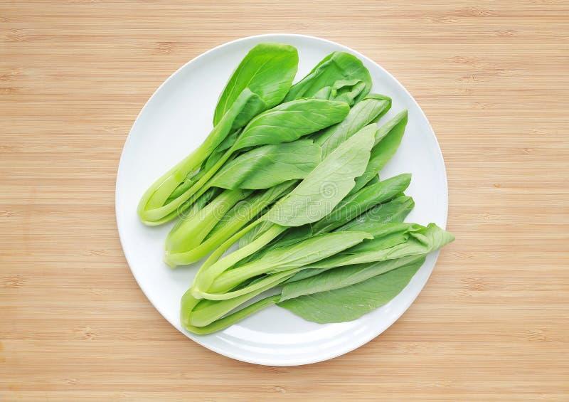 Bok Choy, chou de chine frais du plat blanc sur le fond de conseil en bois photographie stock