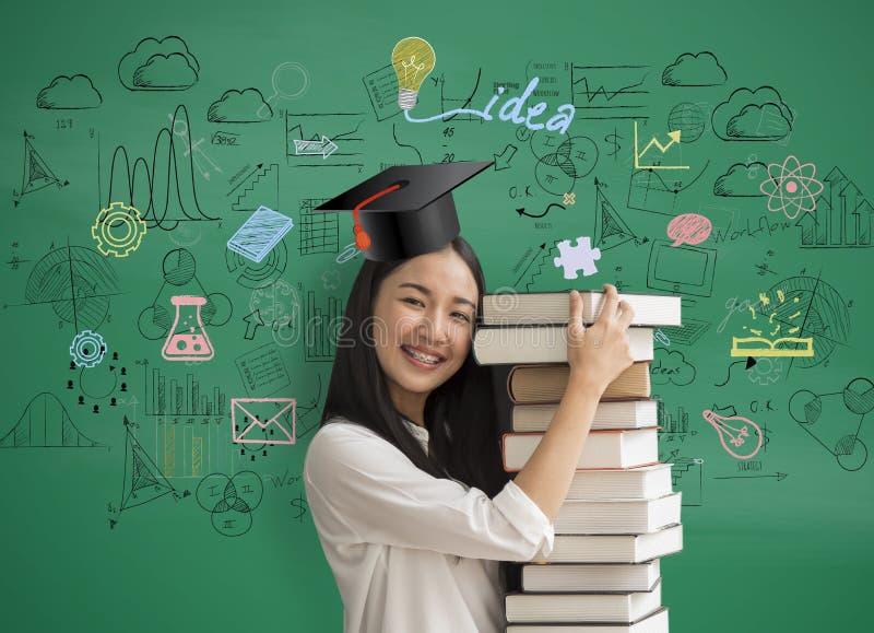 Bok för innehav för Asien kvinnastudent med med avläggande av examenhatten på matematik arkivfoto