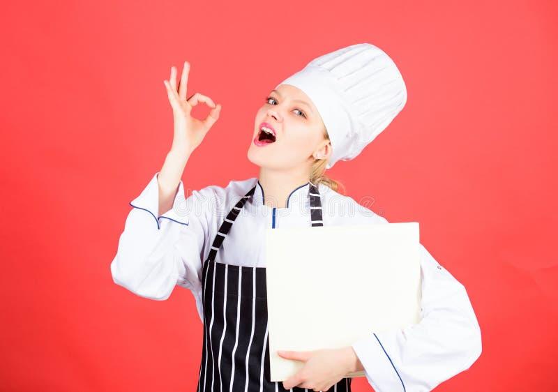 Bok för kvinnaläsningkock i kök Spetsar och r?dgivning matlagningmat Läckert och gourmet- Kulinarisk bok för kockförfattare arkivbilder