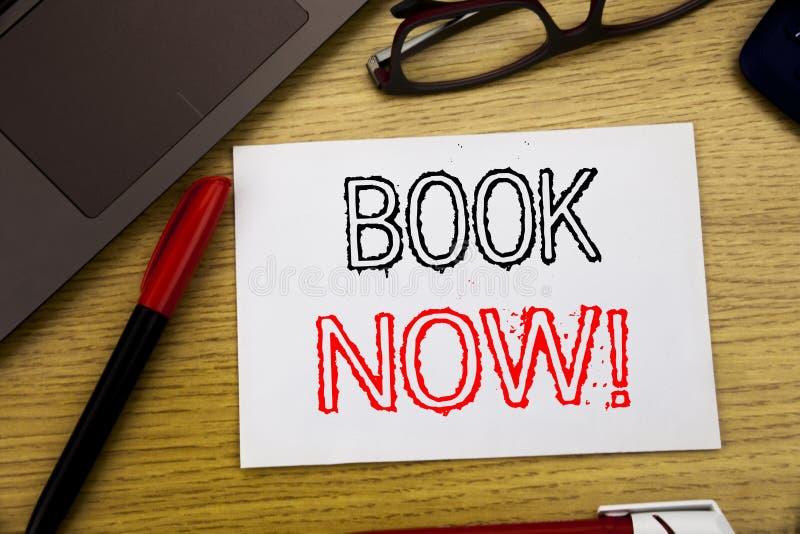 Bok för visning för handskriftmeddelandetext nu Affärsidé för att boka för reservation som är skriftligt på papper, träbakgrund i royaltyfria bilder