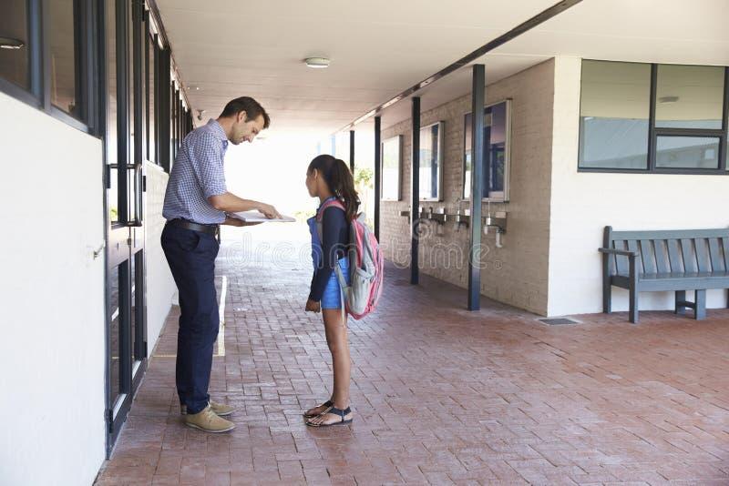 Bok för visning för skolalärare till skolflickan utanför klassrum arkivfoton