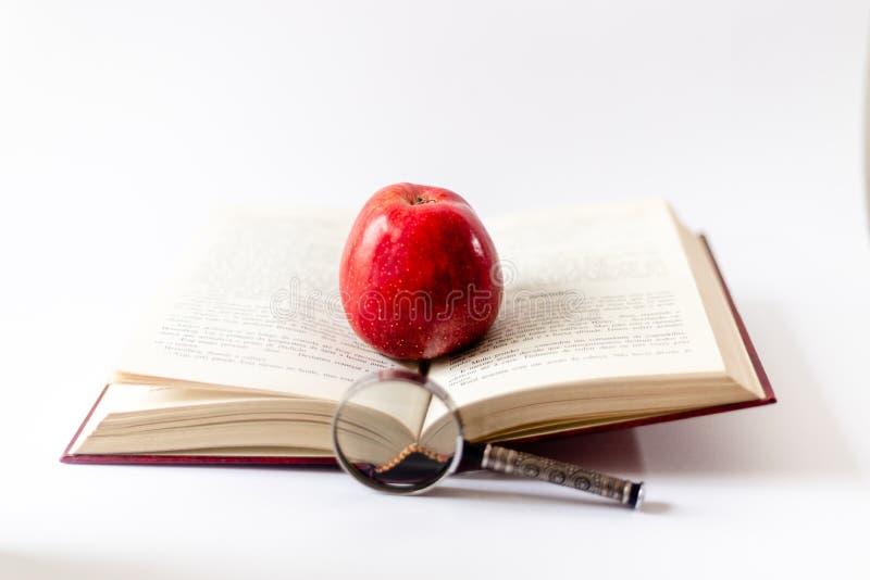 Bok, förstoringsglas och äpple på tabellen Öppna boken med Rött äpple Första gång på skolan pojken lärer den huvudlästa skolalära royaltyfri foto